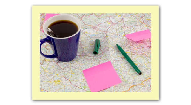 Blue coffee mug and paper with ballpoint on map, preparation for